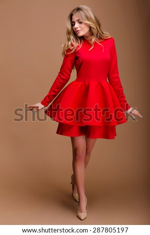 studio portrait of a young blonde girl in a red dress on a white background.. she takes a step. she feels playful and happy