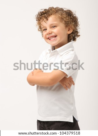 studio portrait of a young boy with his arms crossed smiling