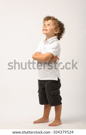 studio portrait of a young boy with his arms crossed smiling and looking up - stock photo