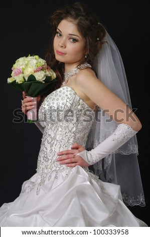 Studio portrait of a young bride wearing a white wedding dress with veil, holding flowers.