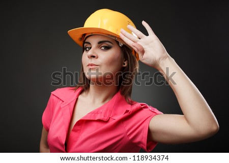 Studio portrait of a young engineer woman with hardhat