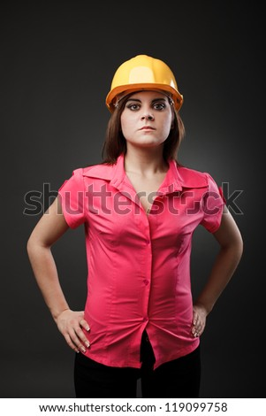 Studio portrait of a young engineer woman with hardhat - stock photo