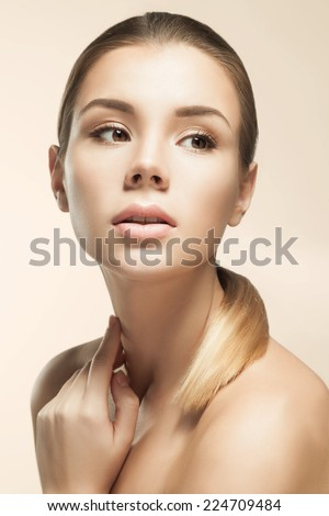 Studio portrait of a young European woman with clear healthy perfect skin on a beige background. Beauty model woman face - stock photo