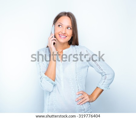 studio portrait of a young happy smiling girl talking on a phone . studio photoshoot. isolated on white .beauty model - stock photo