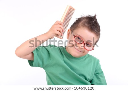 studio portrait of a young kid combing his hair looking happy - stock photo