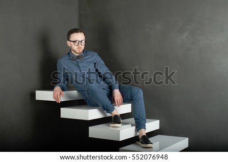 studio portrait of a young man on a dark wall background in a blue shirt and jeans. hipster man, dressed stylishly, with a beard and glasses, sitting on white stairs