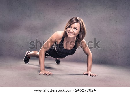 studio portrait of a young woman by doing push-ups - stock photo