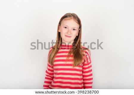 Studio portrait of adorable little girl of 8-9 years old, wearing coral color stripes pullover, standing against white background - stock photo