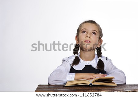 Studio portrait of adorable small school girl looking up.
