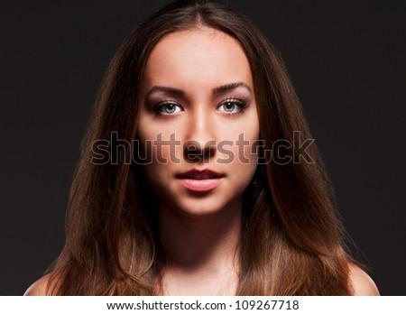 studio portrait of alluring woman over dark background - stock photo