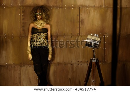 Studio portrait of an African American woman with golden makeup and sunglasses - stock photo