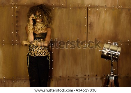 Studio portrait of an African American woman with golden makeup and sunglasses posing holding hands near face - stock photo