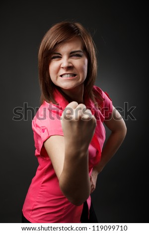 Studio portrait of an aggressive young woman showing her fist - stock photo