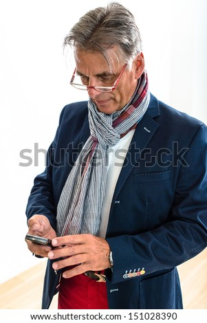 Studio portrait of an attractive and stylish pensioner (is 68 but seems younger) wearing glasses and checking his mobile phone - stock photo