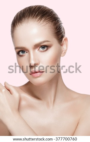 Studio portrait of attractive model with professional makeup on pink background. Perfect fresh skin. Blue eyes. Brunette hair. Not isolated - stock photo