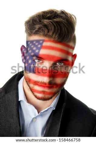 Studio portrait of attractive young man with face painted with Stars and Stripes, the American flag - stock photo