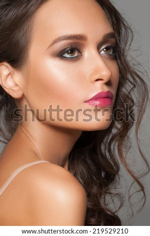 Studio portrait of attractive young woman with stylish makeup and wavy hairstyle - stock photo
