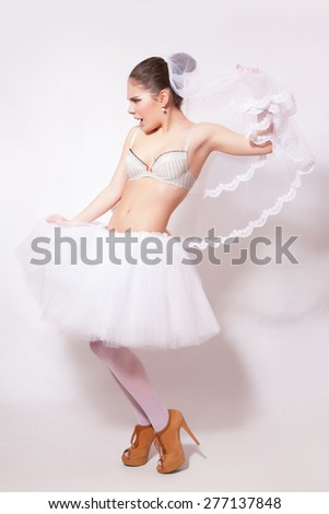 Studio portrait of beautiful angry bride wearing in a white skirt and veil, against gray background - stock photo
