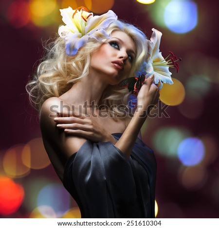 studio portrait of beautiful blonde and tropical butterfly sitting on her hand on dark red background