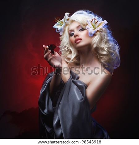 studio portrait of beautiful blonde with blue eyes in gray cloth wearing flowers in her hair and tropical butterfly sitting on her hand on dark red abstract background - stock photo