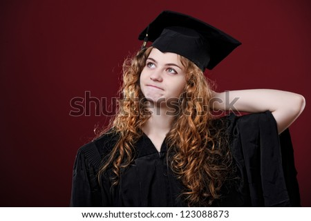 Studio portrait of beautiful curly female graduating student dressed in cup and gown.