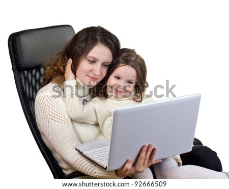 Studio portrait of beautiful little girl and her mother sitting on black leather armchair with laptop. Isolated on white background.