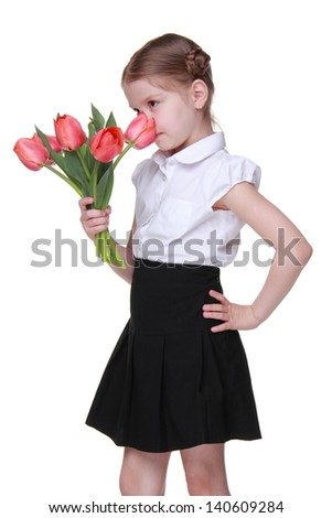 Studio portrait of beautiful sweet little schoolgirl holding red tulips/Cheerful schoolgirl wearing white blouse and black skirt and holding bouquet of flowers on Mothers Day - stock photo