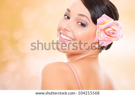 studio portrait of beautiful woman with rose in her hair against blurred background - stock photo
