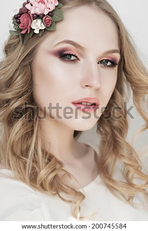 Studio portrait of beautiful young blonde girl with flowers in hair and makeup, beauty concept - stock photo