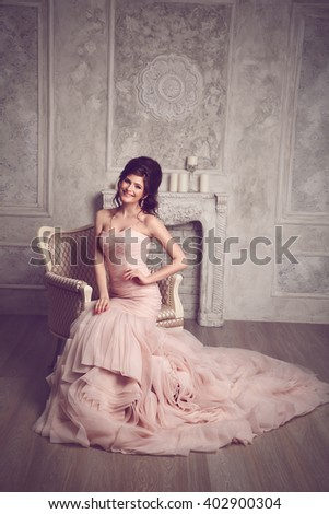 Studio portrait of beautiful young bride in pink dress. Perfect make-up and hairstyle