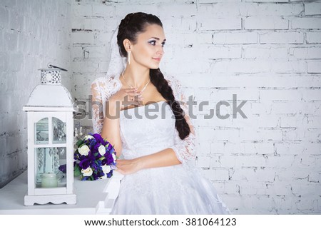 Studio portrait of beautiful young brunette bride in white wedding dress touching her necklace