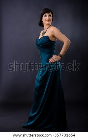 Studio portrait of beautiful young woman wearing dark blue evening dress, posing with hands on hip, smiling. - stock photo