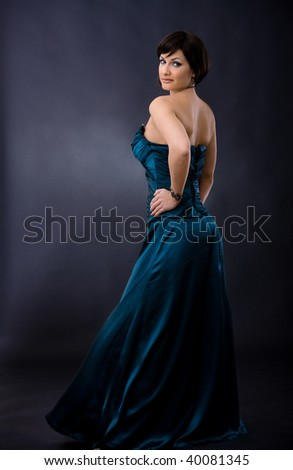 Studio portrait of beautiful young woman wearing dark blue evening dress, posing with hands on hip, smiling, looking back. - stock photo