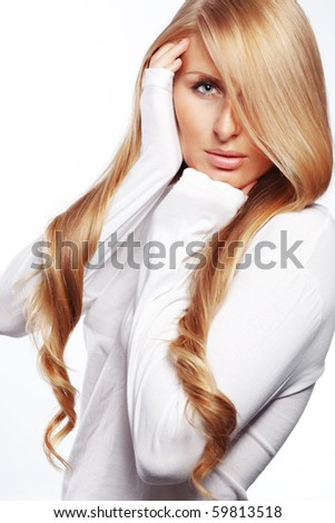 Studio portrait of beautiful young woman with long gold hair - stock photo