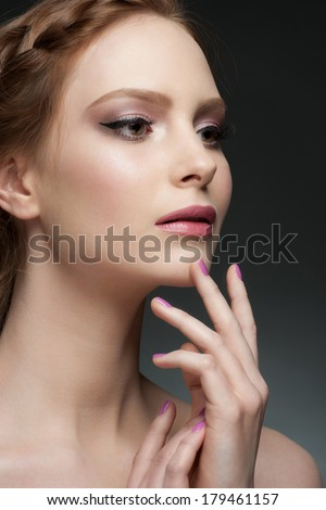 Studio portrait of beautiful young woman with stylish makeup and manicure