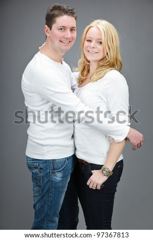 Studio portrait of casual young couple wearing white shirt isolated on grey background