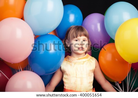 Studio portrait of Caucasian blond little girl with colorful balloons - stock photo