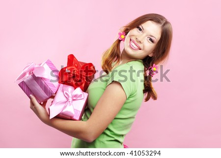 Studio portrait of cheerful cute girl with presents on pink