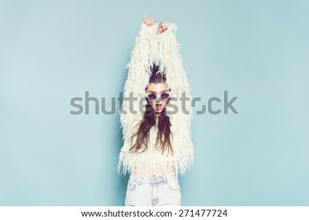 studio portrait of cheerful fashion hipster girl in sunglasses going crazy making funny face and dancing. Blue color background. - stock photo