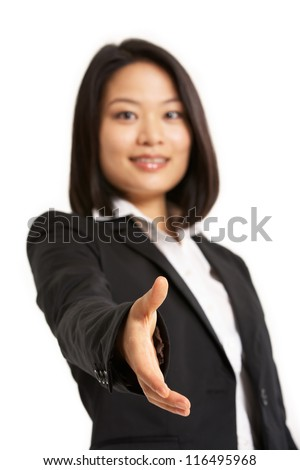 Studio Portrait Of Chinese Businesswoman Reaching Out To Shake Hands - stock photo