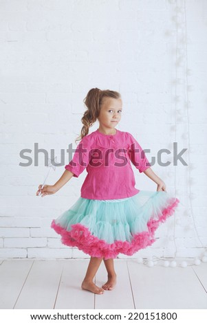 Studio portrait of cute little princess girl wearing holdiday candy tutu skirt holding magic wand - stock photo