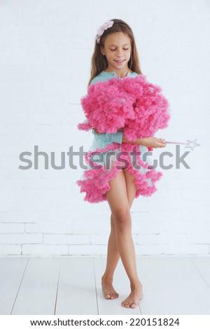 Studio portrait of cute little princess girl wearing holiday candy tutu skirt holding magic wand - stock photo