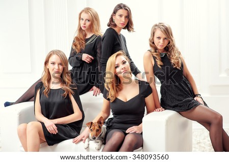 Studio portrait of elegant women's team. Group portrait of 5 attractive caucasian female colleagues wearing black dresses sitting on the white sofa with a little dog - stock photo