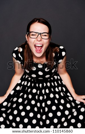 studio portrait of emotional young woman in polka-dot dress over dark background - stock photo