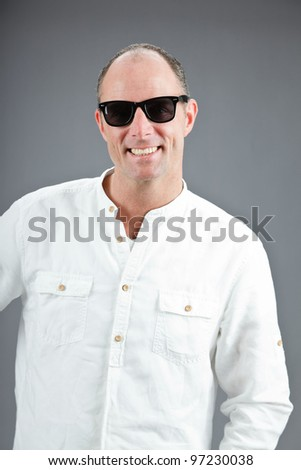 Studio portrait of expressive middle aged man wearing white shirt and sunglasses isolated on grey background - stock photo