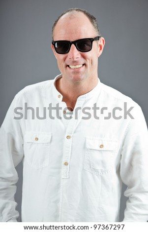 Studio portrait of expressive middle aged man wearing white shirt and sunglasses isolated on grey background