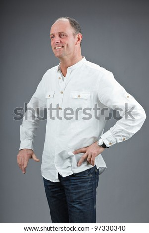 Studio portrait of expressive middle aged man wearing white shirt isolated on grey background