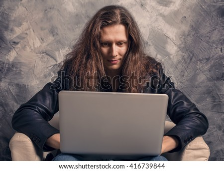 Studio Portrait of fashion business man sitting in chair using laptop computer. Freelance it programmer, hacking, shopping online  - stock photo