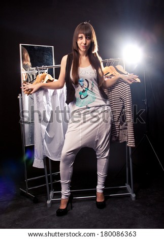 Studio portrait of fashionable woman posing against mirror and hangers with clothes
