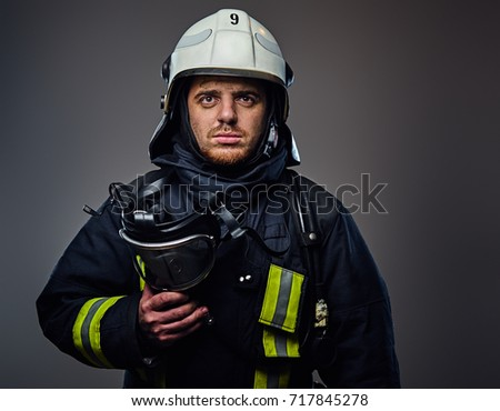 Studio portrait of firefighter dressed in uniform and safety helmet.